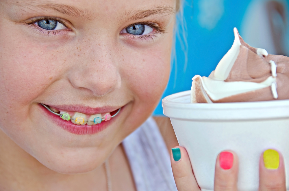 Girl smiling with colored braces and ice cream